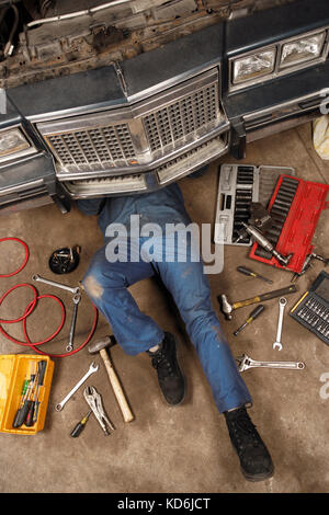 Photo of a mechanic doing repairs under the front of an old car from the early 80's. - Stock Photo