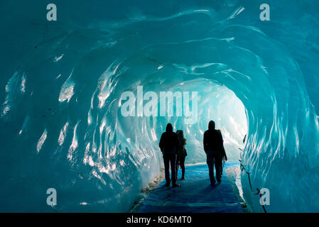 Silhouettes of people visiting thee ice cave of the Mer de Glace glacier,  in Chamonix Mont Blanc Massif, The Alps, - Stock Photo