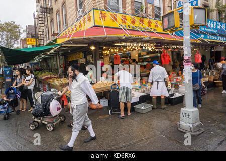 An Orthodox Jewish man walks past a Chinese seafood store on Eighth Avenue in the Sunset Park neighborhood in Brooklyn - Stock Photo