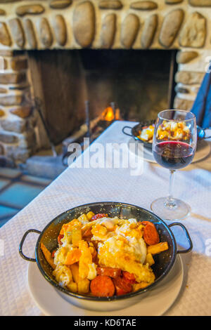 Fried eggs with potatoes and chorizo in a restaurant. Rascafria, Madrid province, Spain. - Stock Photo