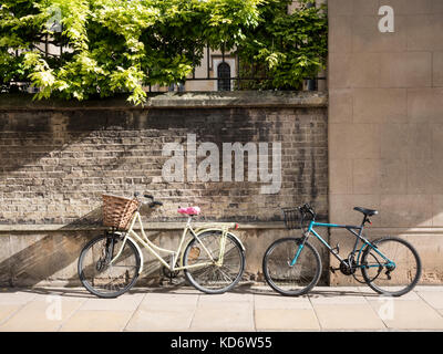 Two bicycles leaning up against the wall of Sidney Sussex College part of Cambridge University UK in autumn sunshine - Stock Photo
