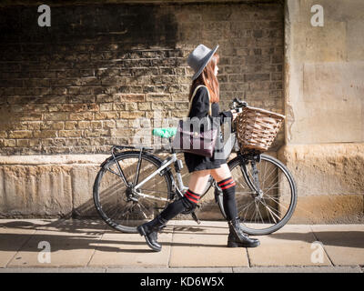 A Japanese woman wearing long socks walks past a bicycle with a basket leaning up against the wall of Sidney Sussex - Stock Photo