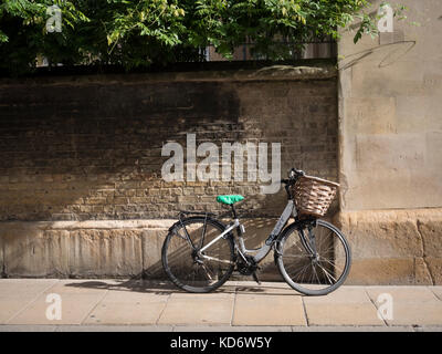 A bicycle with a basket leaning up against the wall of Sidney Sussex College part of Cambridge University UK in - Stock Photo
