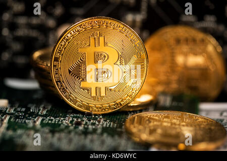 View of golden coins of Bitcoin cryptocurrency on a circuit board background - Stock Photo