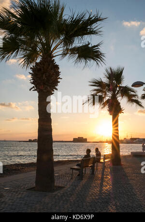 Tourists watch the sunset on the promenade in Kato Paphos, Paphos, Cyprus - Stock Photo