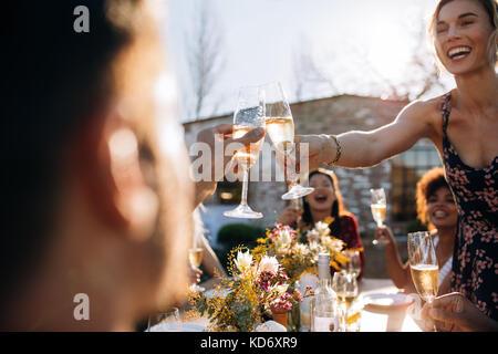 Smiling young woman toasting champagne with friend during an outdoor party. Young people enjoying at  party with - Stock Photo