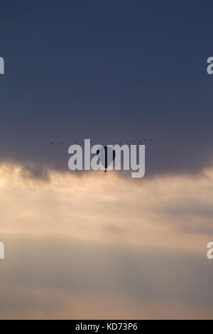 A solitary balloon takes flight in the evening sky, rising high amidst clouds. Evening light conditions create silhouette - Stock Photo