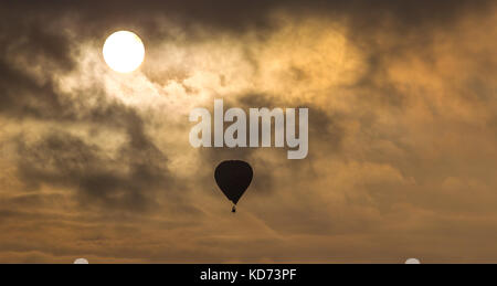 Hot air balloon takes peaceful flight at sunset, rising high amidst fluffy clouds. Bright sun shines through upper - Stock Photo
