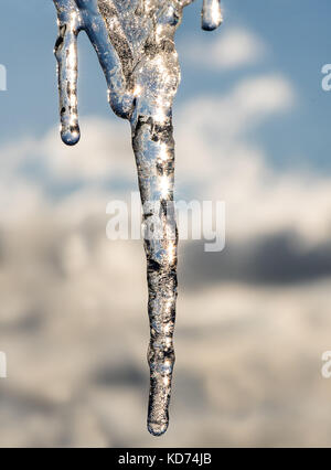 Icicle close up against the sky. Sunshine rays in an icicle. - Stock Photo
