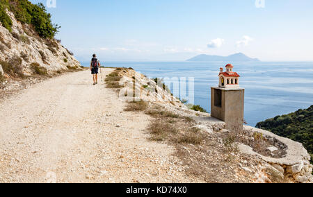 A female walker passing a roadside shrine in the form of a church on the island of Ithaka in the Ionian Islands - Stock Photo