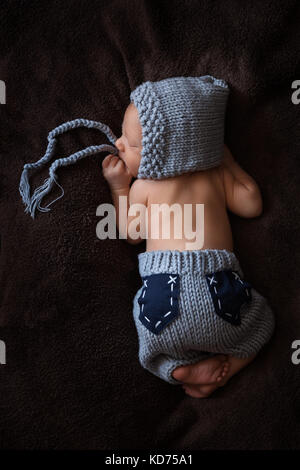 Newborn baby in a gray knitted suit sleeps in a beautiful pose - Stock Photo