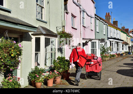 Postman on rounds in row of terrace houses on high street in small English market town of Thornbury, South Gloucestershire - Stock Photo