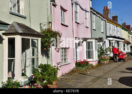 Postman making deliveries on rounds in row of terrace houses on high street in small English market town of Thornbury, - Stock Photo