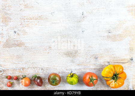 border of ancient variety of tomatoes from the smallest to the bigest on old white painted wooden background copy - Stock Photo