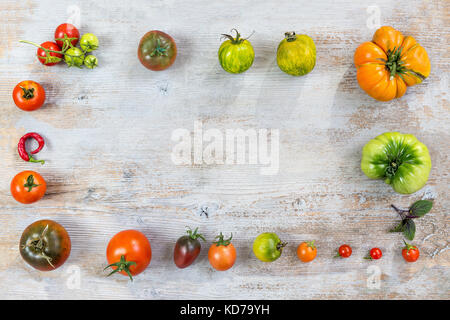 Frame of Various different color organic homegrown tomatoes on old wooden painted background. Background with red, - Stock Photo