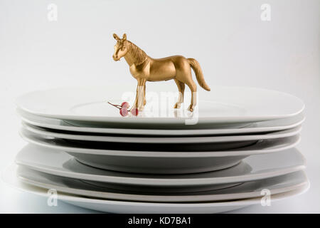 Dishes Plates stacked white and clean tableware and gold horse, conceptual food - Stock Photo
