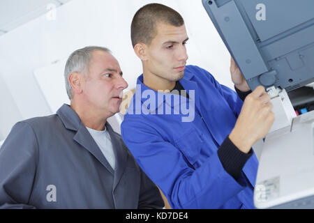 technician and apprentice stand in industry - Stock Photo