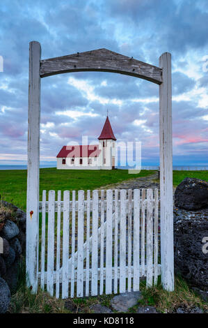 Hellnar Church framed by the front white gate around midnight, Summer, midnight sun, Snaefellsnes Peninsula, Iceland, - Stock Photo