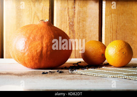 pumpkins and two arange in sunlight on wooden background - Stock Photo