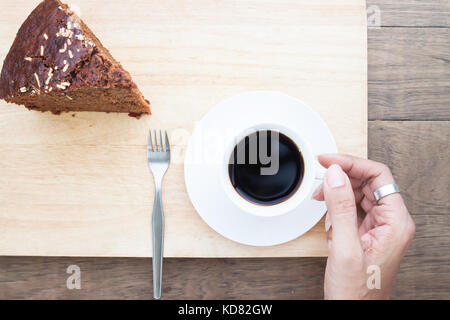 Creative flat lay of woman hand with coffee cup and chocolate cake - Stock Photo