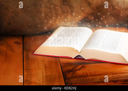 Old open book with magic light on wooden table - Stock Photo
