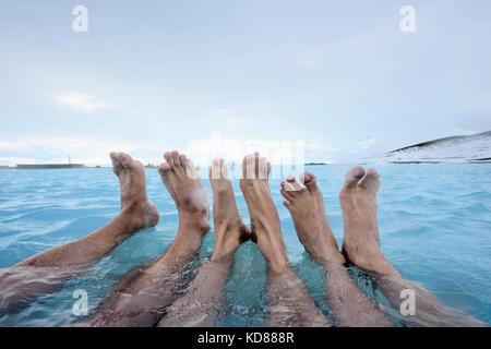 People relaxing in geothermal pool outdoors - Stock Photo