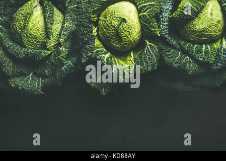 Raw fresh uncooked green cabbage over dark background, top view, copy space - Stock Photo