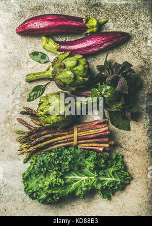 Flat-lay of green and purple fresh vegetables variety over concrete background, top view. Local seasonal produce - Stock Photo