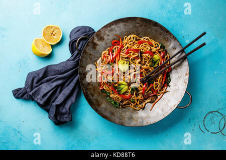 Udon stir fry noodles with oyster mushrooms and vegetables in wok pan on blue background - Stock Photo