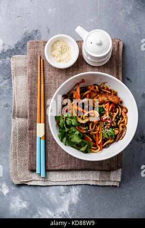 Udon stir fry noodles with Chicken meat and vegetable in bowl on concrete background - Stock Photo
