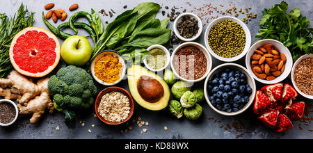 Healthy food clean eating selection: fruit, vegetable, seeds, superfood, cereal, leaf vegetable on gray concrete - Stock Photo