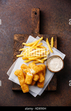 Fish fingers and Chips british fast food with tartar sauce on dark background - Stock Photo