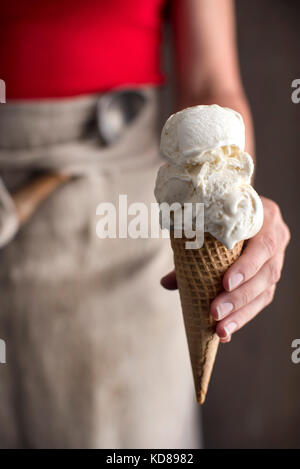 Woman wearing a red shirt and linen apron holding out a freshly scooped vanilla ice cream cone. - Stock Photo