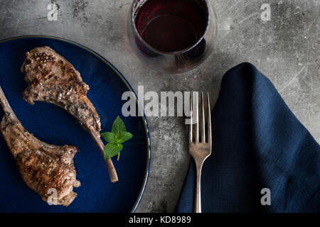 Roasted lollipop lamb chops on blue plate. Table setting with navy linen, red wine and rustic metal surface. - Stock Photo