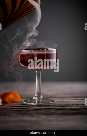 Red cocktail in vintage coupe glass with smoke pouring in on a rustic, gray wood surface. - Stock Photo