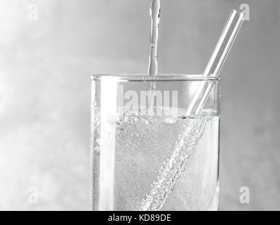 Detail of sparkling water being poured into a clear glass with a clear straw on a gray metal background. - Stock Photo
