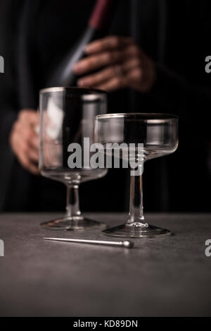Antique, high end wine glasses with sommelier in background with bottle of red wine. - Stock Photo