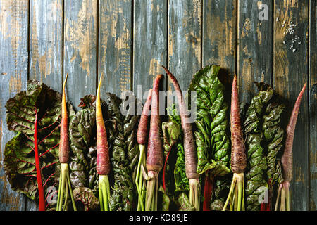 Raw organic purple carrot with chard mangold leaves over old wooden plank background. Top view with copy space. - Stock Photo