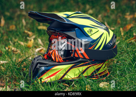 motorcycle helmet with glasses for protection dry fallen leaves over greem grass. Automne - Stock Photo