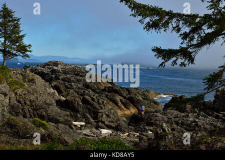 A young man exploring the  rocky coast line along the west coast trail near Ucluelet on Vancouver Island British - Stock Photo