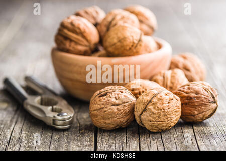 Tasty dried walnuts and nutcracker on old wooden table. - Stock Photo