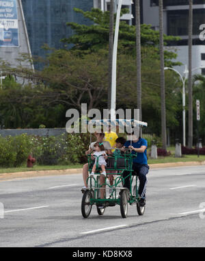 Family on a four wheel cycle traffic free area on Sunday in Panama City - Stock Photo