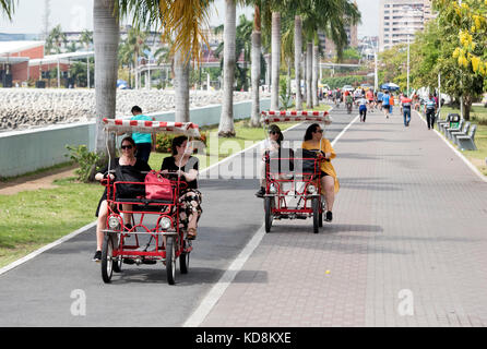 Four wheel fun bicycle carts in the traffic free area on Sunday in Panama City - Stock Photo