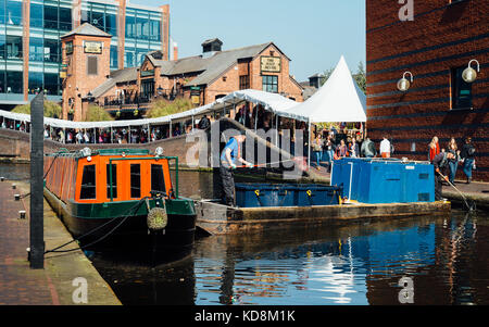 A man cleans up debris from the Birmingham's main canal, overlooking a traditional British pub - Stock Photo