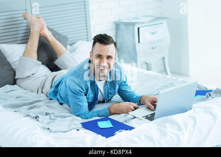 Friendly looking freelancer enjoying working from home - Stock Photo