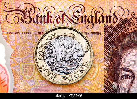 New British pound coin on a plastice £10 note - Stock Photo