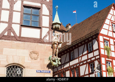Pilatushaus (Pilatus house) in the old town of  Nuremberg. A statue of St. George in golden armour  defeating the - Stock Photo