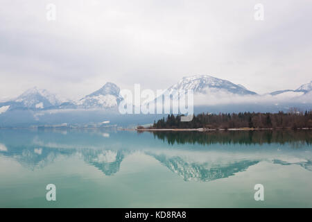Wolfgangsee, a beautiful lake in austrian alps. Winter, cloudy sky, mountains reflecting in water. Austria. - Stock Photo