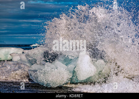 Waves breaking over natural ice sculptures on the Jokulsarlon black sand beach in South Iceland - Stock Photo