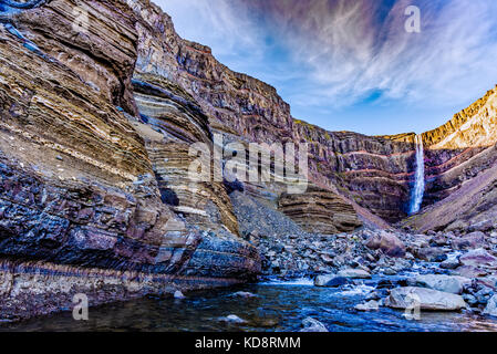 Hengifoss waterfall in Iceland featuring spectacular red rock strata formed by numerous volcanic eruptions - Stock Photo